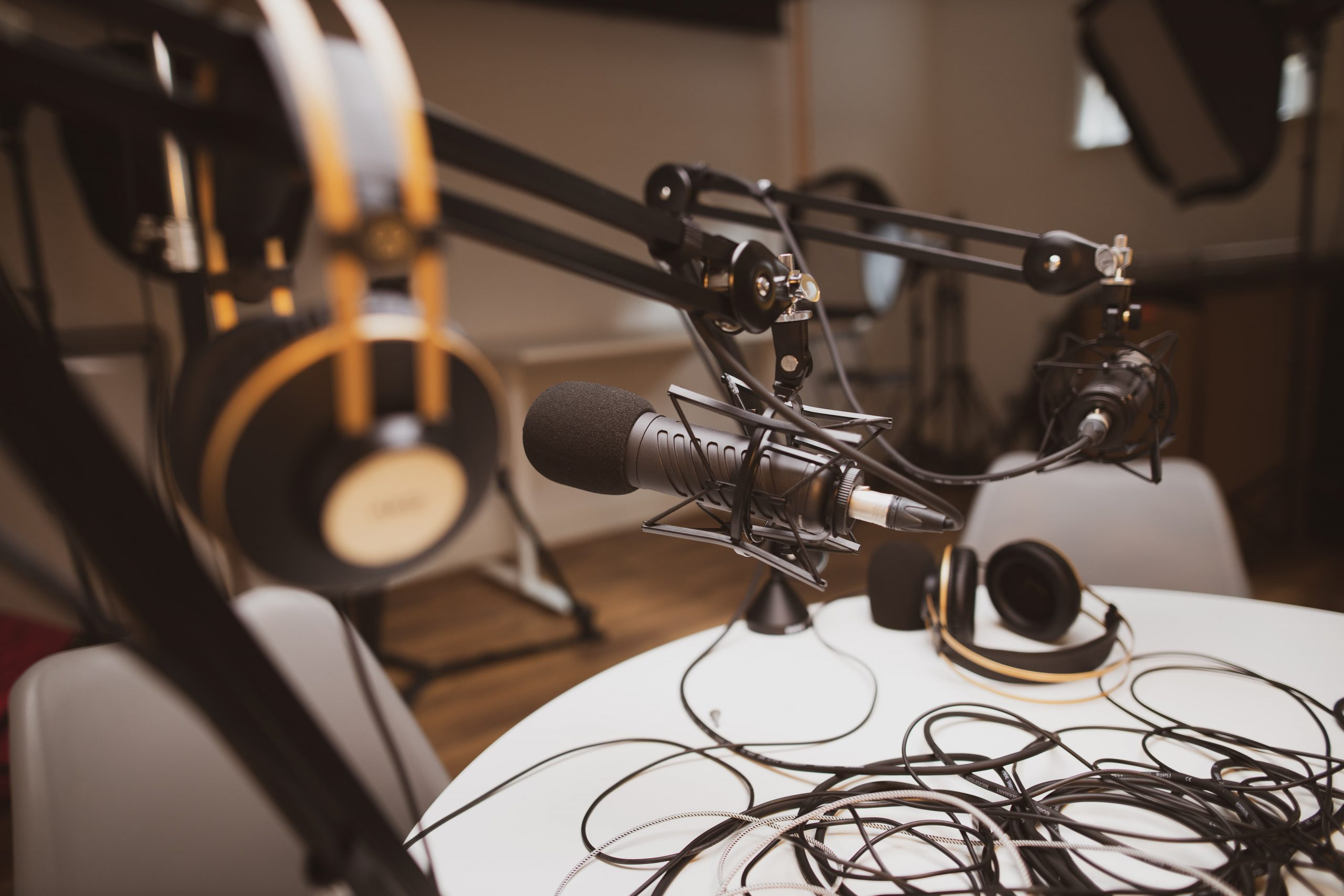 Black microphone and two headphones on a white round table